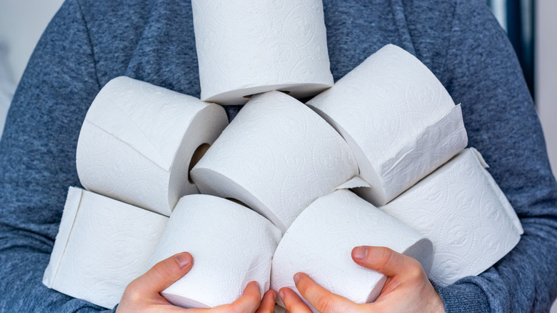Person carrying several rolls of toilet paper