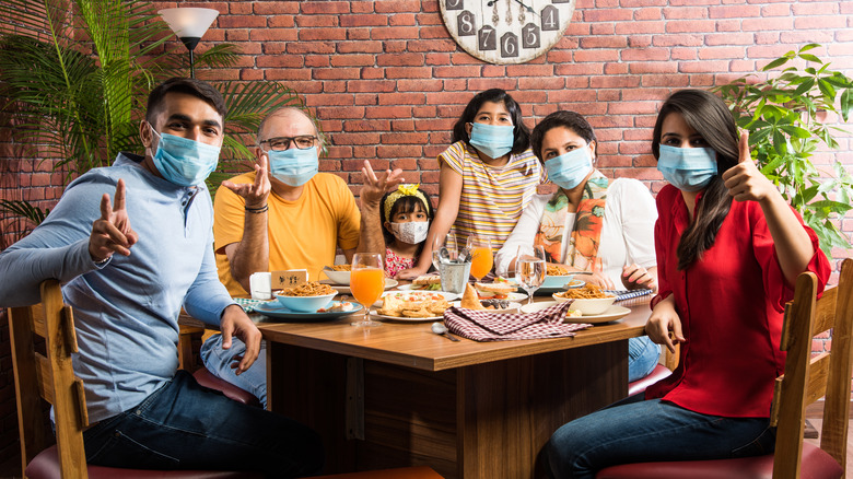 Family of diners wearing face masks