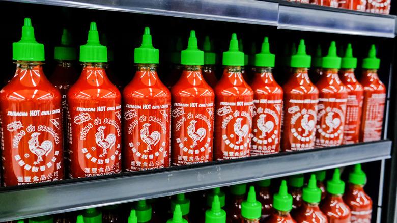 Sriracha bottles with green lids on store shelves