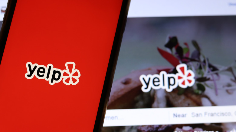 Yelp icon on phone and laptop screen