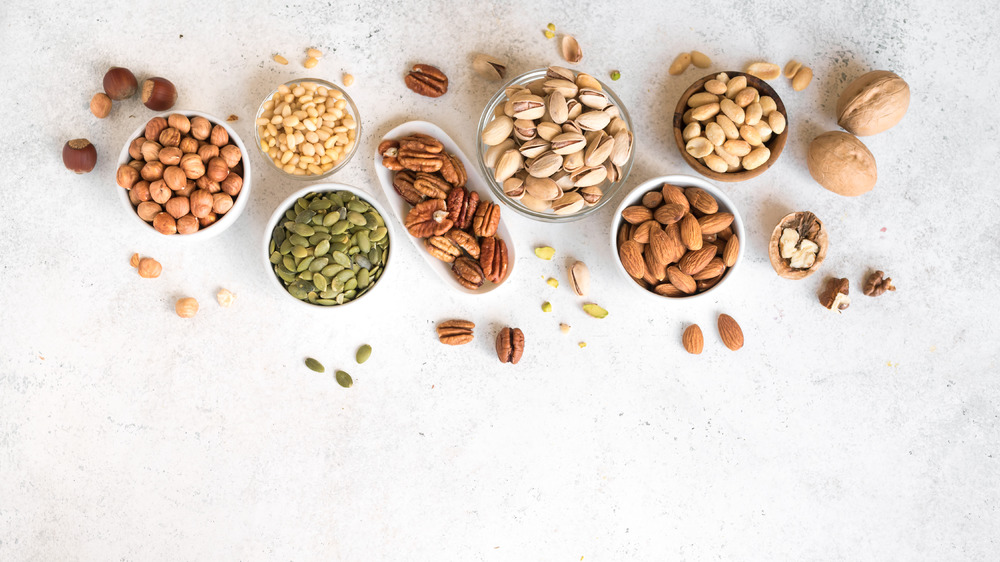 Different kinds of nuts in white bowls