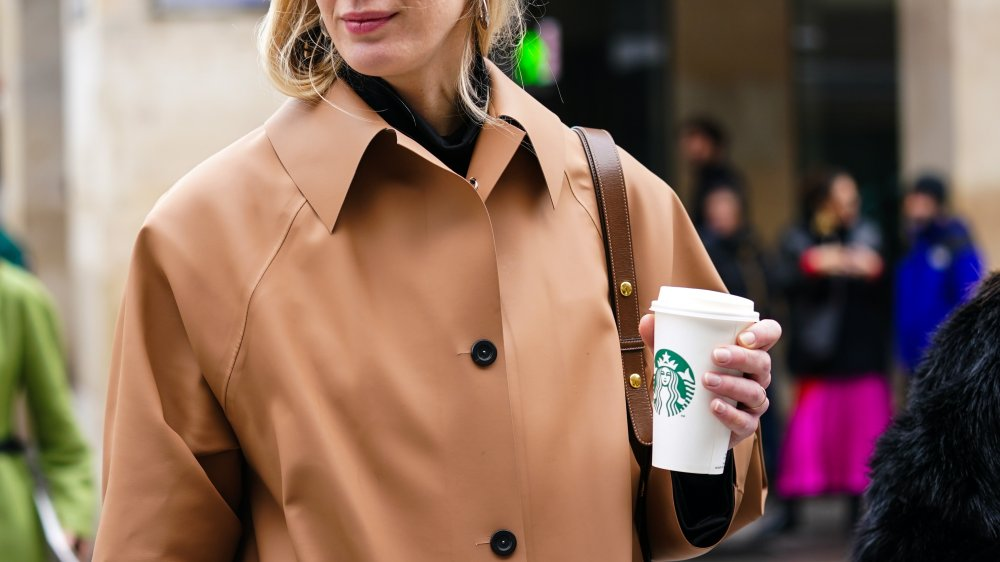 Woman holding cup of Starbuck's coffee