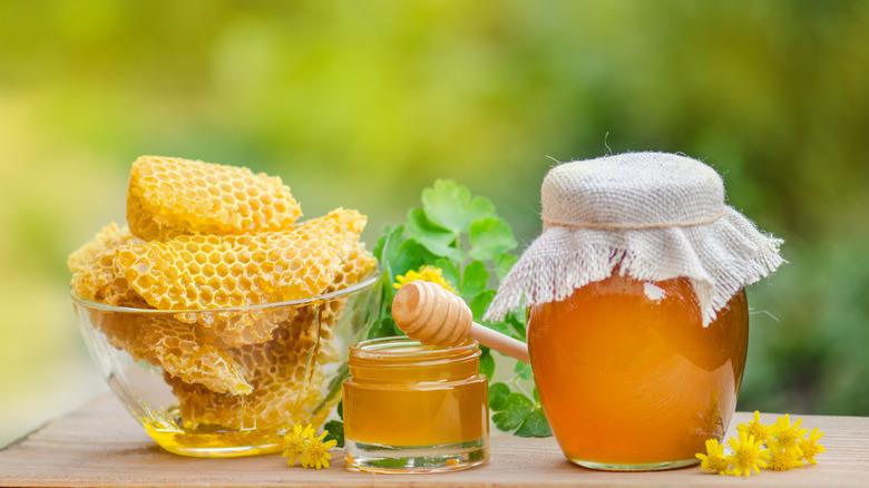 Bowl of honeycombs next to jars of honey