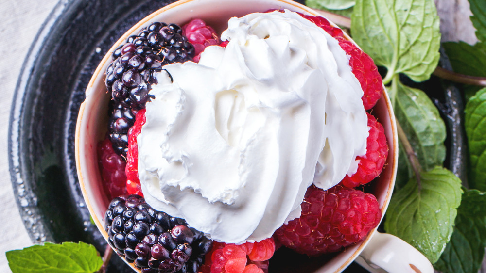 Whipped cream over raspberries and blackberries
