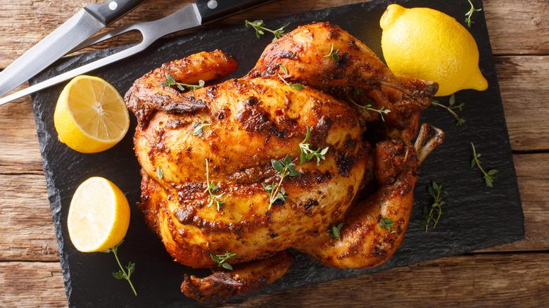 Roast chicken on cutting board with lemons