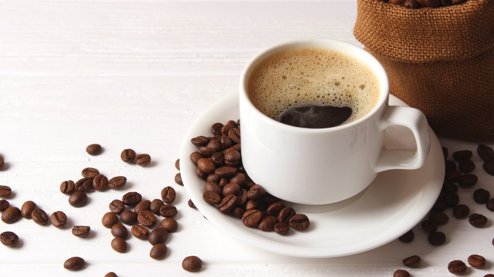 A cup of coffee surrounded by beans