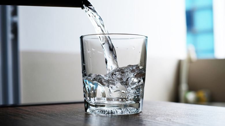 Water being poured into glass jar on wood table