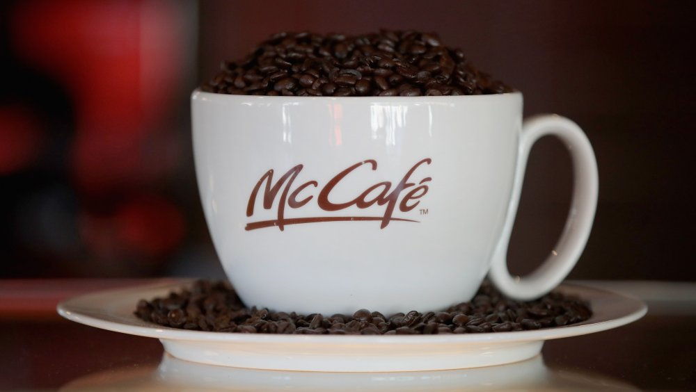 A McCafe cup full of coffee beans