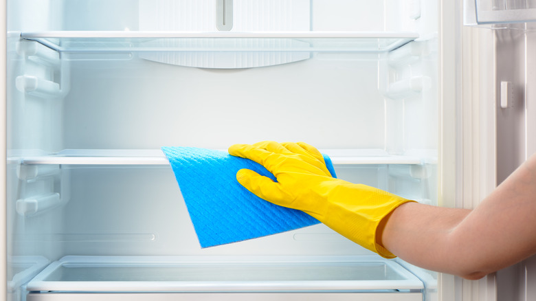 Person wiping out refrigerator
