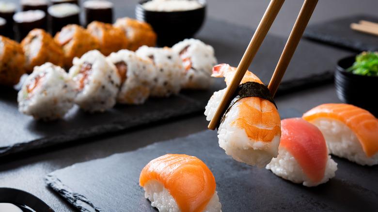 Chopsticks lifting shrimp sushi off black slab