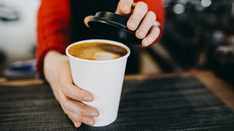 Barista holding a takeaway coffee