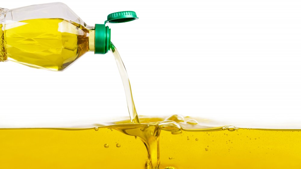 plastic bottle pouring more cooking oil into a pool of oil