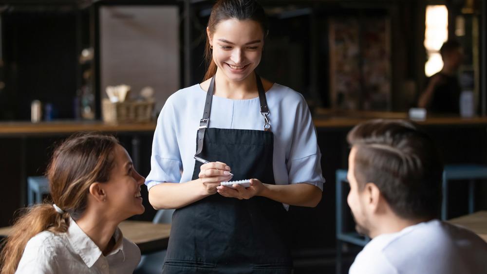 Waiter taking order at restaurant