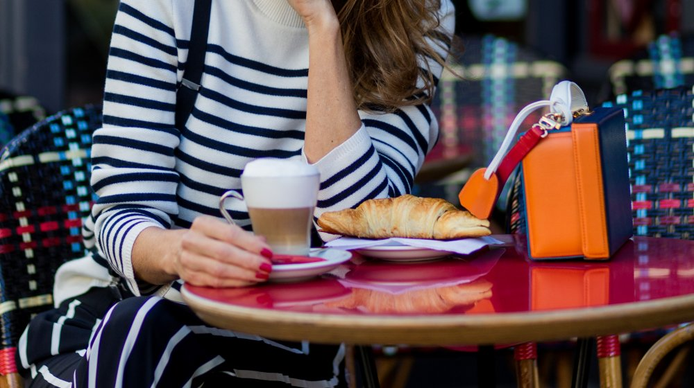 Person sitting at a cafe with a croissant and coffee