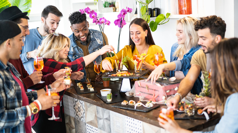 Group of people laughing and enjoying small plates of food
