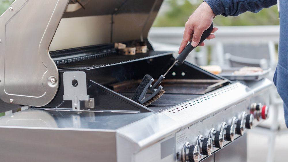 Gas grill being cleaned