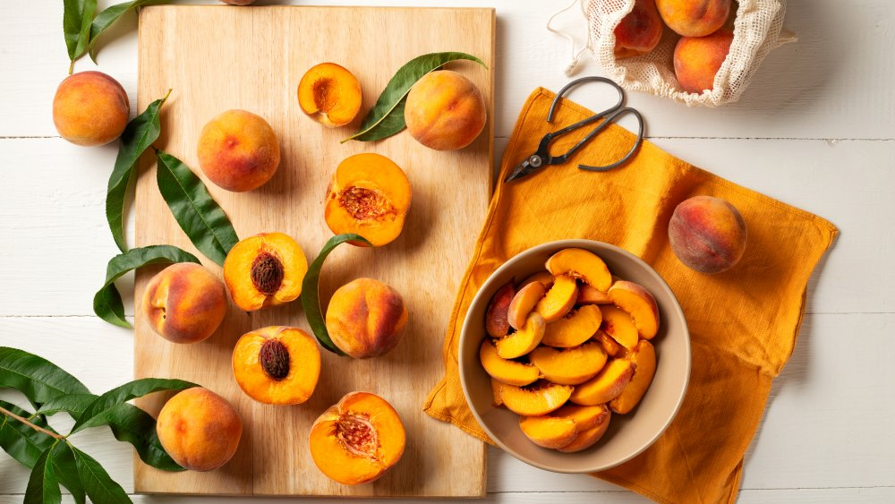 whole peaches and cutting board with halved peaches