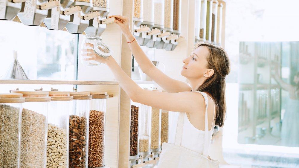 woman purchasing nuts from bulk bin