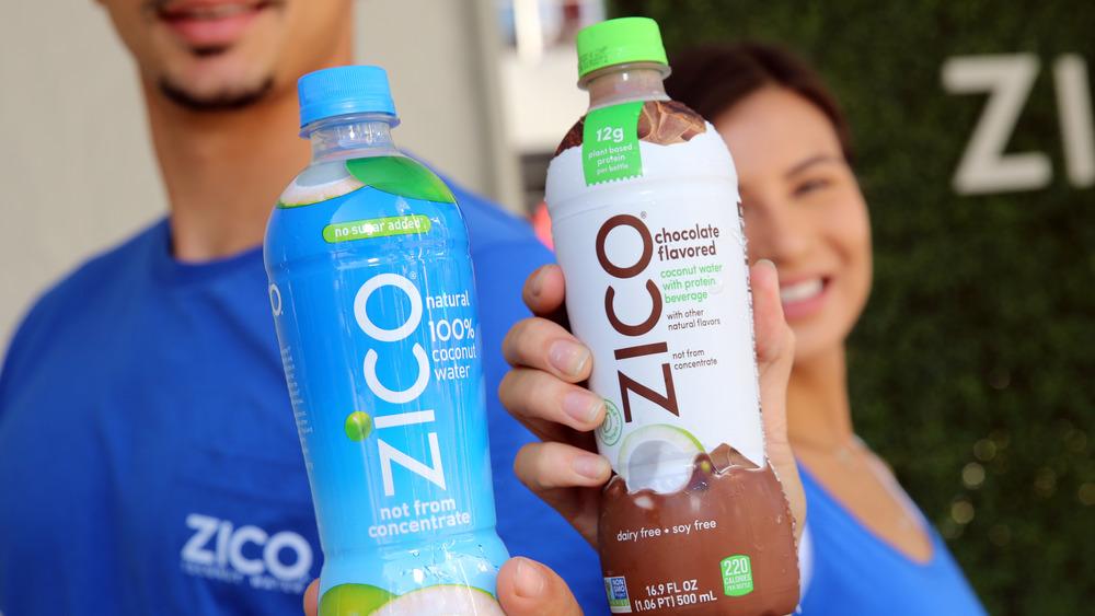 people holding zico bottles